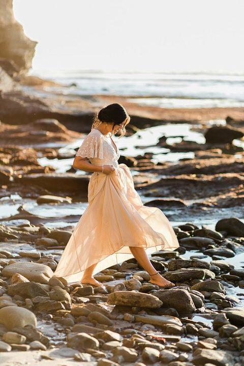 Elopement bride walking across the rocks in Sunset Cliffs Park, California