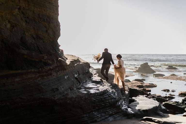 Elopement couple Climbing cliffs together in Sunset Cliffs Park