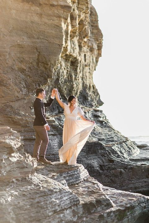 Groom spinning his bride at Sunset Cliffs Elopement