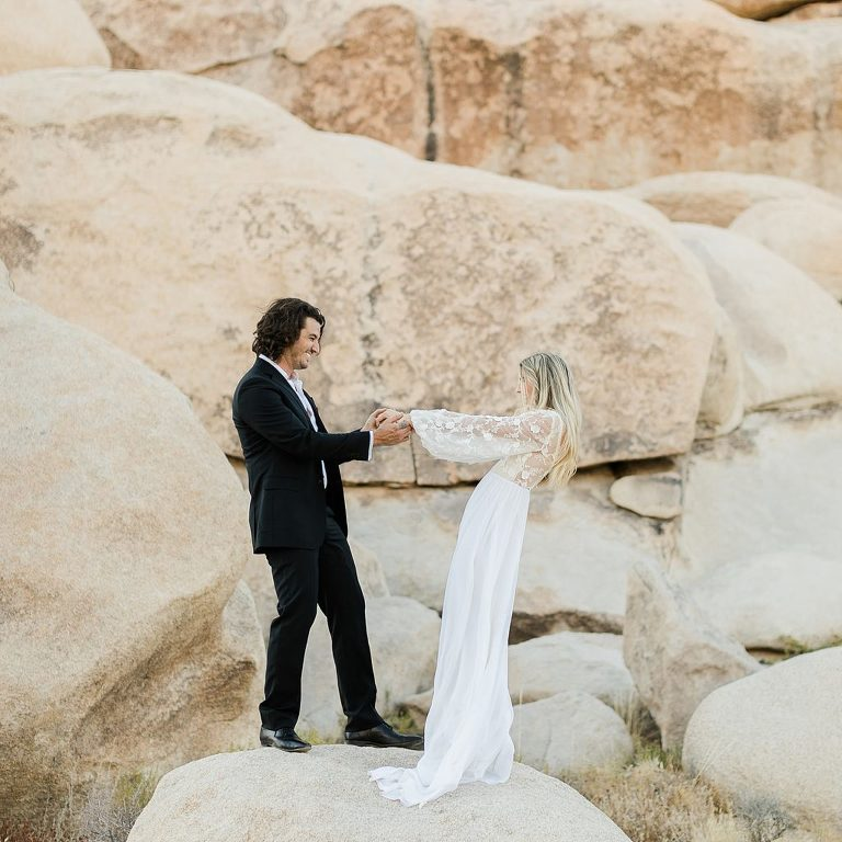 bride and groom on rock formations at Joshua Tree Elopement